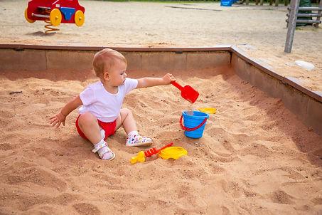 adorable-toddler-girl-playing-with-sand-sandbox-playground_edited.jpg