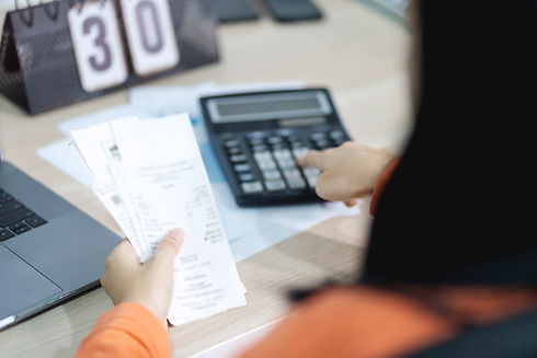 woman-holding-bill-using-calculator-calc