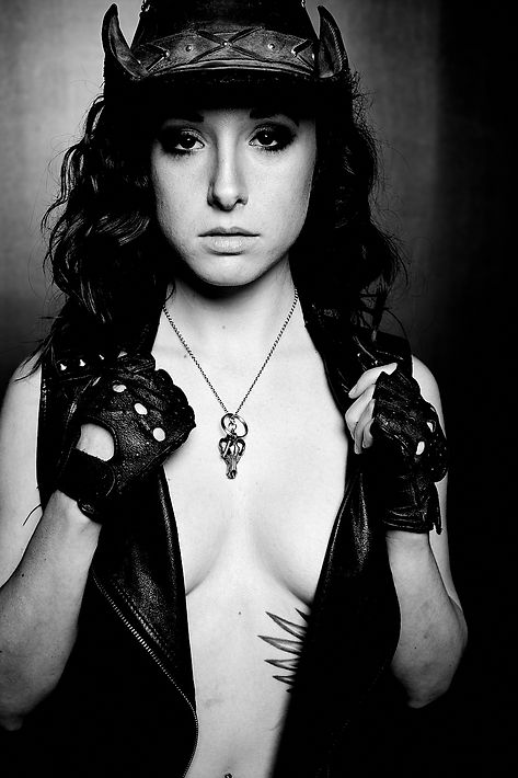 B&W profile shot. Misress Wolfe in a leather vest, gloves, and cowboy hat. A silver wolf skull necklace and key around her neck. Topless under the vest, looking into the camera. Photo by Mark Dektor
