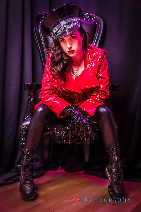 Mistress Wolfe sitting in a throne, wearing shiny black pants, clawed gloves, and a cap with a red vinyl jacket. Photo by 2G Photography.