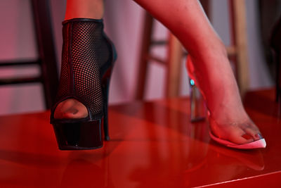 A black fishnet ankle boot heel and a white/clear pump in reddish light, close up. Photo by DK Vision