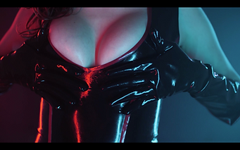 Mistress Wolfe's breasts in a black and red latex dress. Photo by DK Vision