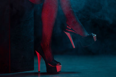 Black and cream heels in red and black light. Tight fishnets worn underneath. Profile view. Shot by DK Vision