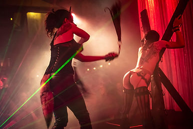 On the stage in red light with green lasers, Mistress Wolfe (dressed in a corset, wolf mask, and tail) flogs a tattooed woman cuffed to a St Andrews Cross. From a performance at Bar Sinister in Los Angeles.