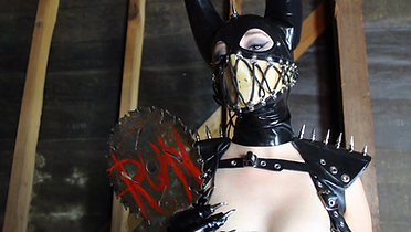 """Headshot of Mistress Wolfe in a Dayne Henderson latex mask with lacing stitched across her face. Spiked latex shoulder pads can be seen, along with a rusty sawblade paddle in her hands reading """"RUN"""" in red letters."""