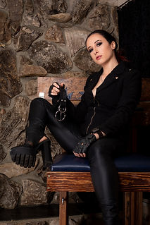 Mistress Wolfe posing on a wood and blue spanking bench against a stone background. Slightly reclined, a chunky heel lifted onto the bench. Hair pulled back, wearing a black blazer, pants, and leather gloves. Holding a black belt.