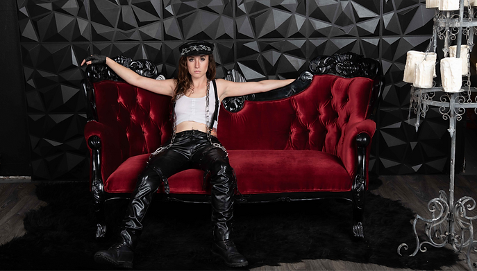 Mistress Wolfe reclining on a gothic black and red sofa, wearing a leather cap, a white cropped shirt, black leather suspenders, shiny black pants, Dr Martens, and a chain. Photo by Carpe Lucem Photography