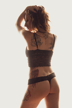 Backlit by white Mistress Wolfe poses with her back to the camera in black lingerie, holding her hair up as she peeks back over her shoulders. Her body decorated with beautiful tattoos. Photo by RVM Photo