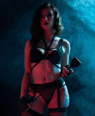 Bathed in red and bluish light, Mistress Wolfe stands in a bra, panties, garter, fishnets, and a strappy nylon harness. Surrounded by smoke effects, holding a long leather crop. Photo by DK Vision