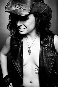 Mistress Wolfe in a leather vest and leather cowboy hat, shirtless underneath. Eyes downcast with a slight grin, oozing Daddy energy. Shot by Mark Dektor
