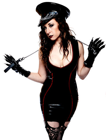 Mistress Wolfe in a black and red latex dress with a chain leash. Photo by Mark Dektor.