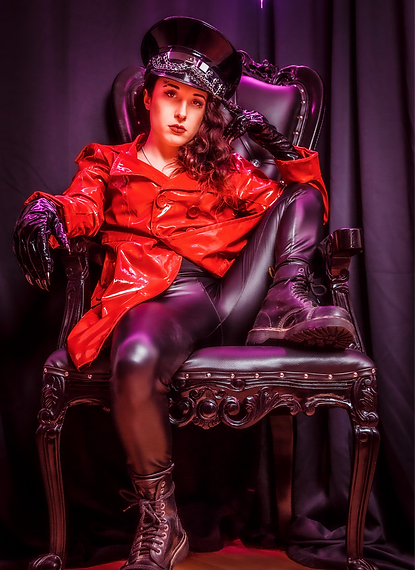 Mistress Wolfe reclined in a throne, wearing shiny black pants, clawed gloves, and a cap with a red vinyl jacket. Photo by 2G Photography.