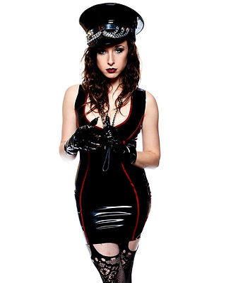 Mistress Wolfe in color against a white background, wearing a black latex dress with red trim, vinyl gloves, fishnet stockings, and a vinyl black cap with chain details. Holding a leash around her neck, staring seductively into the camera. Photo by Mark Dektor