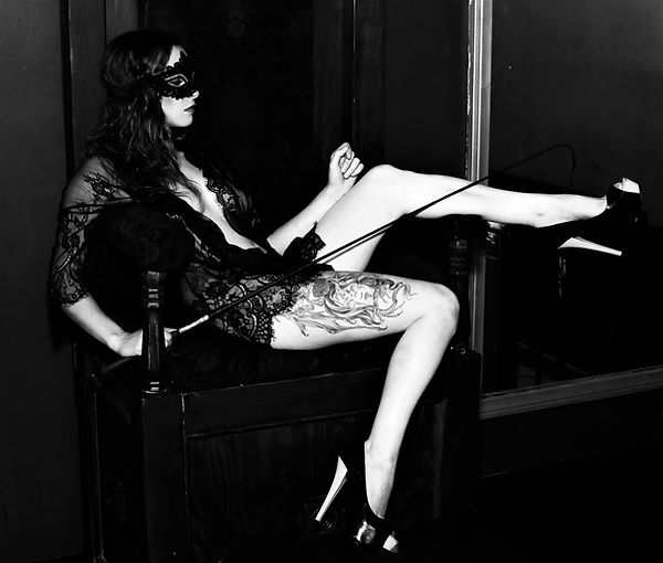 B&W. Mistress Wolfe reclined in a chair holding a horse whip, wearing a lace kimono, a masquerade mask, and cream and black heels. Photo by Moonwalk Photography.
