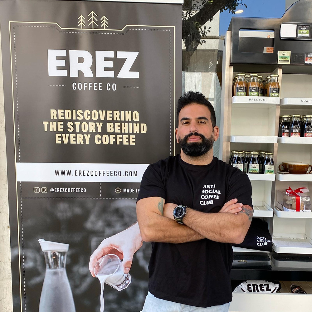 #Meet_the_Oleh Matan Bouganim standing in front of a sign of his coffee shop, Erez