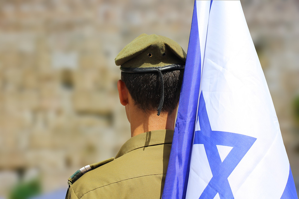 An male IDF soldier standing at the Western Wall with an Israeli flag on Yom HaZikaron