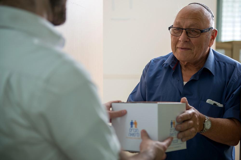Haverim L'Refuah delivering a box of medicine to an older gentleman