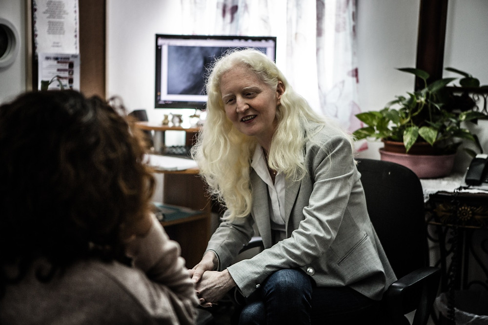 A woman with white blond hair sitting in an office speaking with another woman