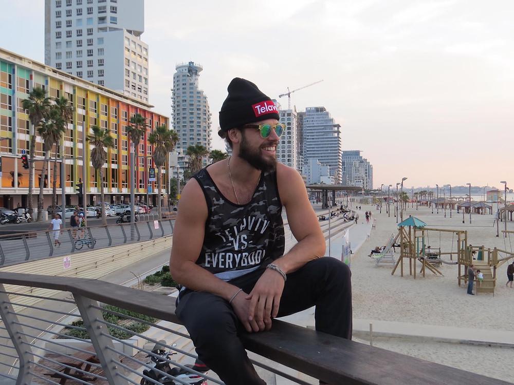 Oleh Johnny Denver Levine sitting on a fence railing on the beach in Tel Aviv