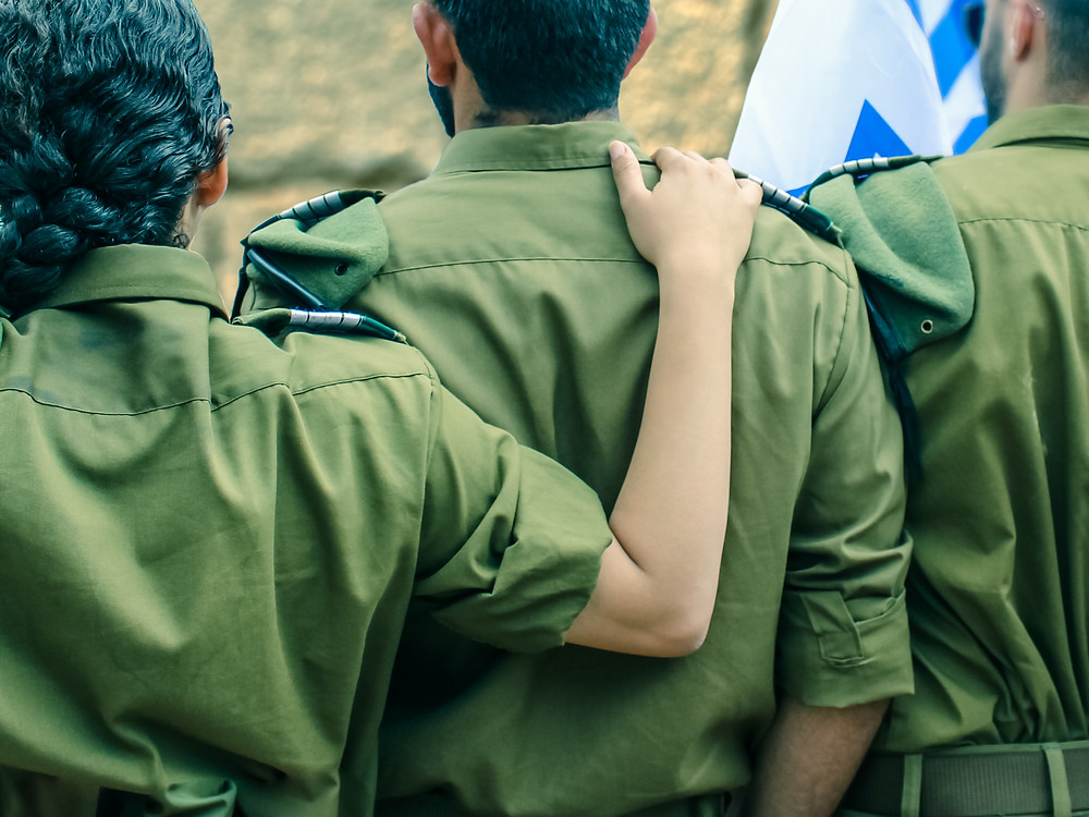 Female IDF soldier with her hand on the back of a male IDF soldier on Yom HaZikaron