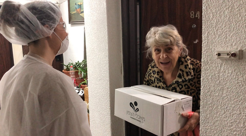 A Leket volunteer delivering a food package to an elderly woman at her door