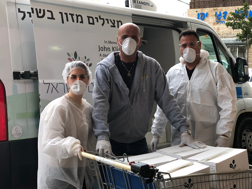 3 Leket volunteers with a shopping cart of boxes next to an open van