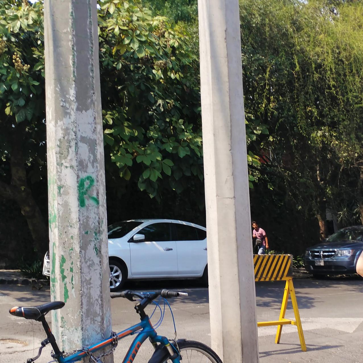 A bike parked by a street pole