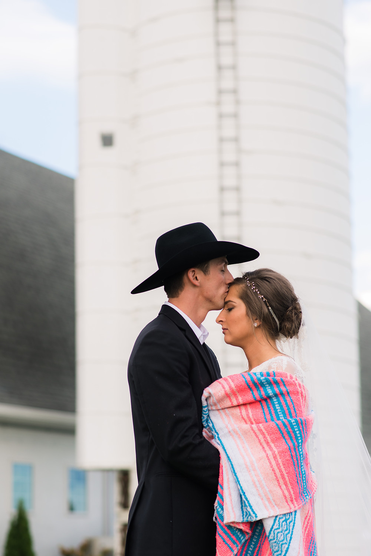 Silo at Vanderwende acres wedding venue cowboy hat groom kissing brides forehead