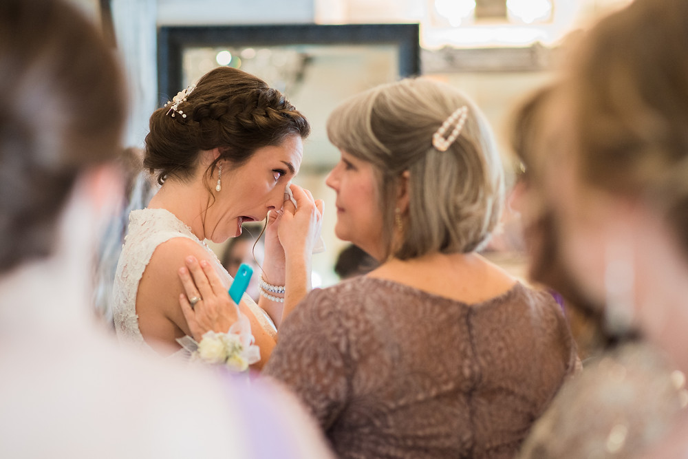 Delaware bride wipes tears from her eyes, while her mom comforts her, in the bridal suite at Kylan Barn on Marylands Eastern Shore.