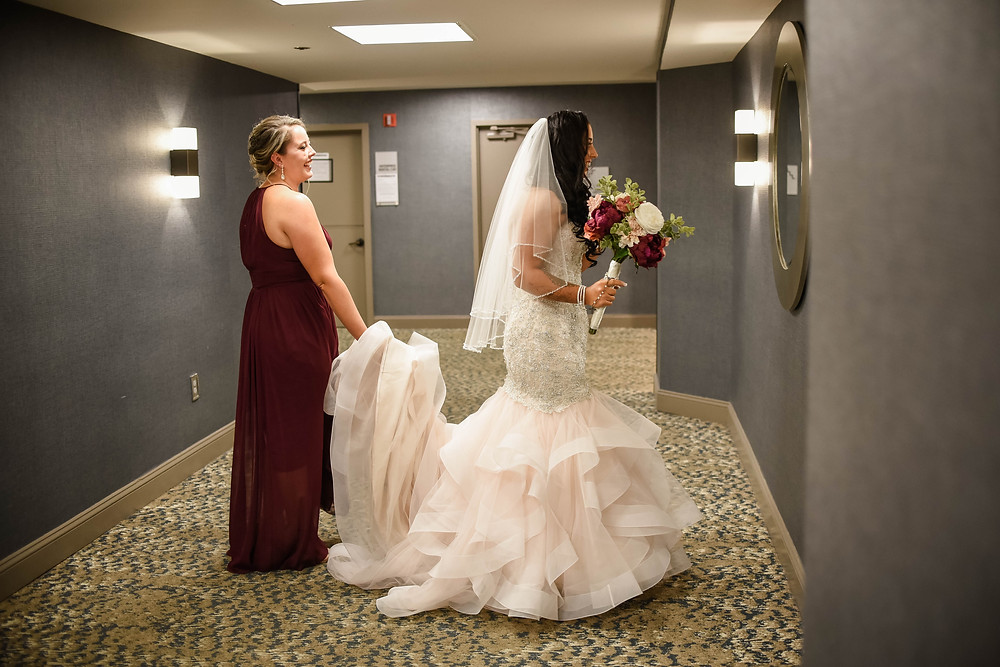 """Everyone was dressed and ready so it was time for bridal portraits.  As this bride walked down the hallway she caught a glimpse of herself in the hotel's mirror.  She stopped dead in her tracks and looked at herself in the mirror, """"I didn't know I was this beautiful!""""  Everyone smiled because they all knew she was this beautiful."""