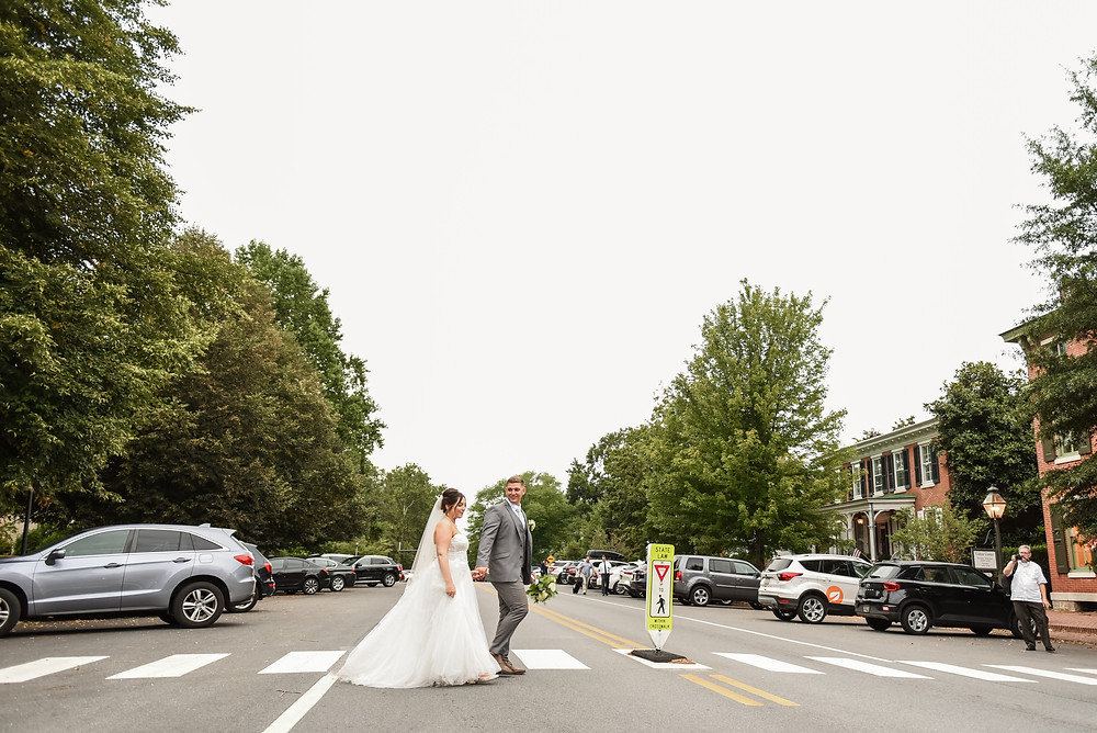 bride and groom walking across the crosswalk in the historic downtown Odessa. Grandpa can be seen on the far right holding his camera.