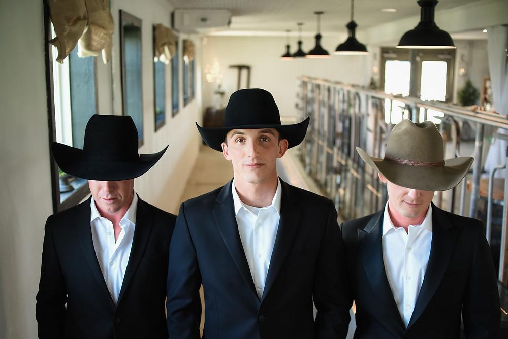 cowboy hat groomsmen in dairy barn at charming wedding venue in Delaware's Seaford