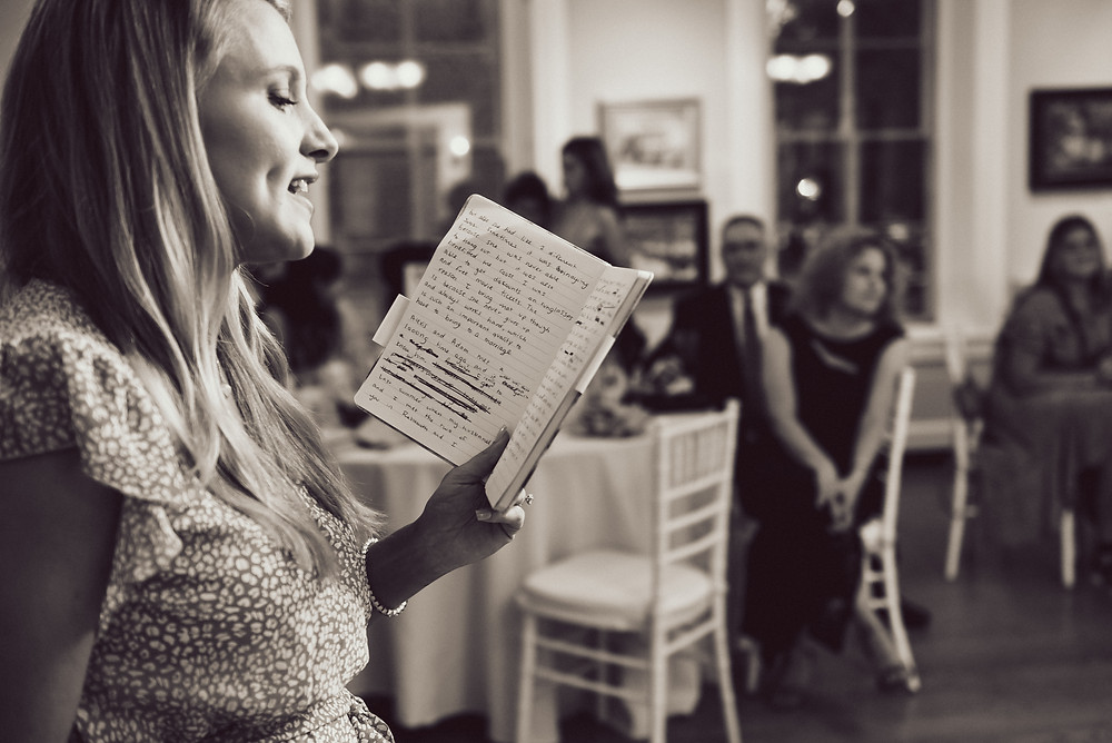 Bride's friend is standing before family and friends reading from a notebook where she wrote and made edits. Four entire lines are scirbbled out on the notebook's page.