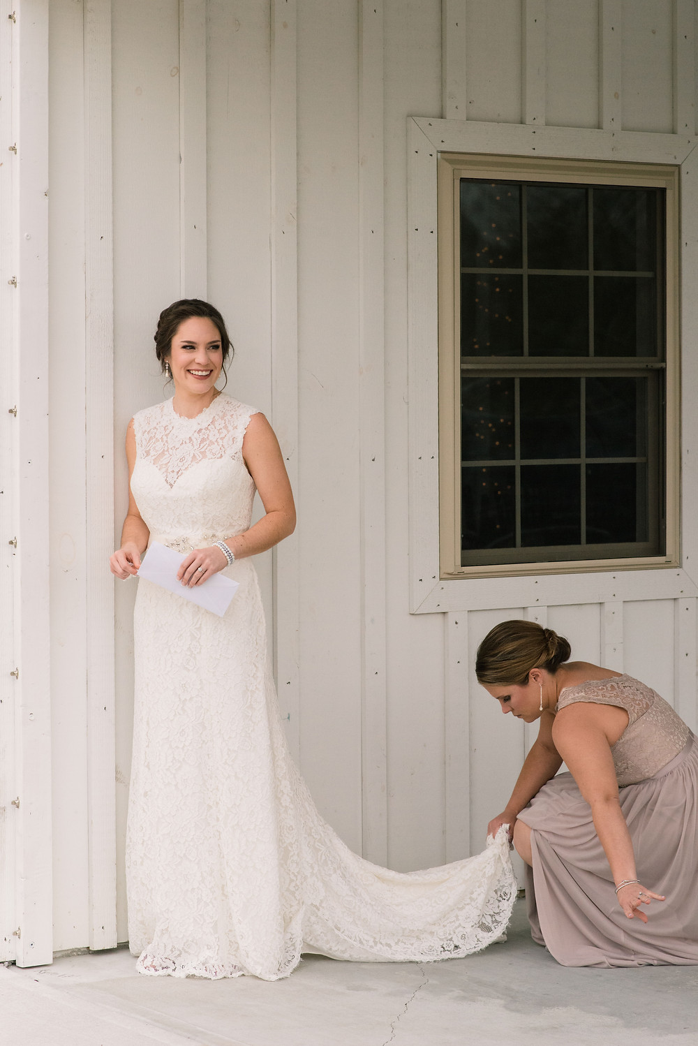 Bride has her dress fluffed at the corner of the Kylan Barn before she sees her groom.
