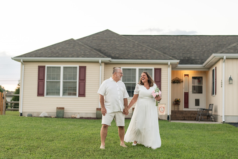 Husband and wife married for 40 years is dressed in wedding dress and casual wedding suit in their front yard laughing and walking.