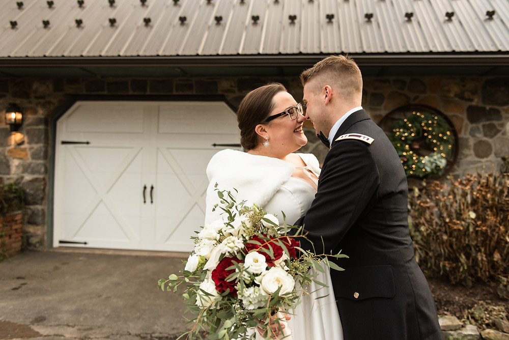 Bride and groom outside by stone wall. Bride is wearing a faux fur shaw over her shoulders while her groom is hugging her around her waist.