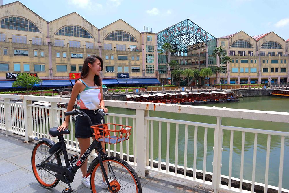Girl standing on bridge near Riverside Point with an SG Bike
