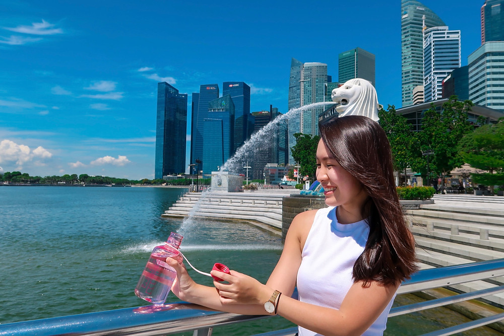 Fun pose in front of Merlion - Collecting water from Merlion using water bottle