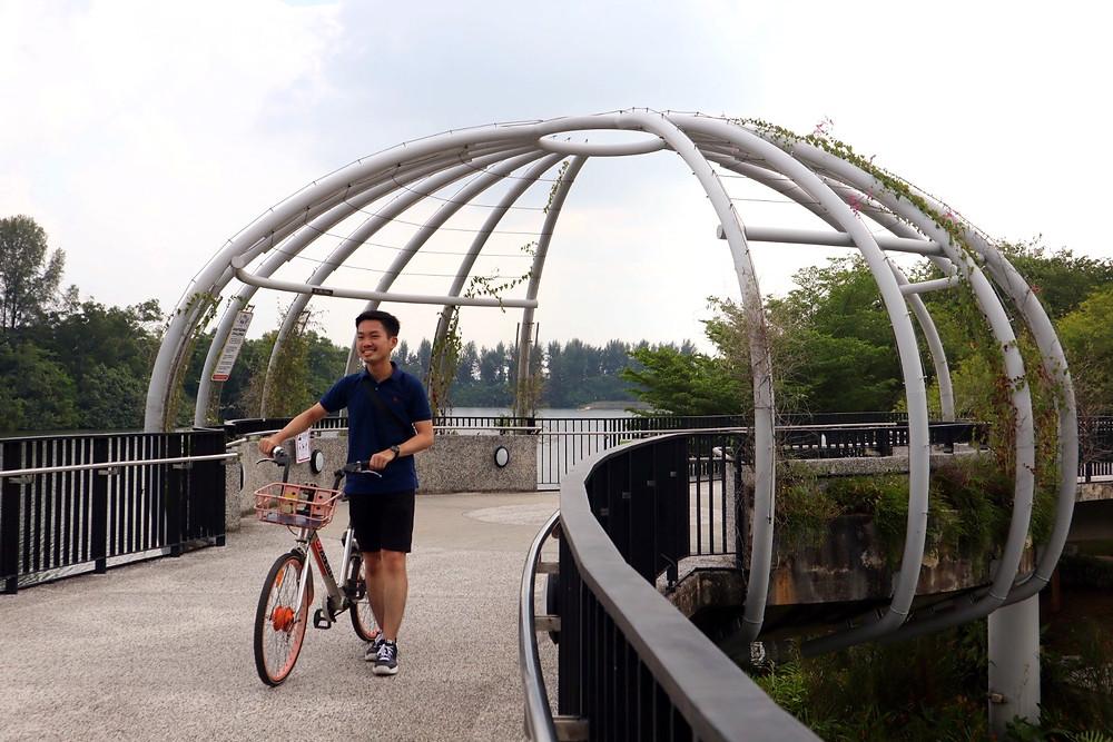 Guy pushing bicycle at Punggol Waterway Park