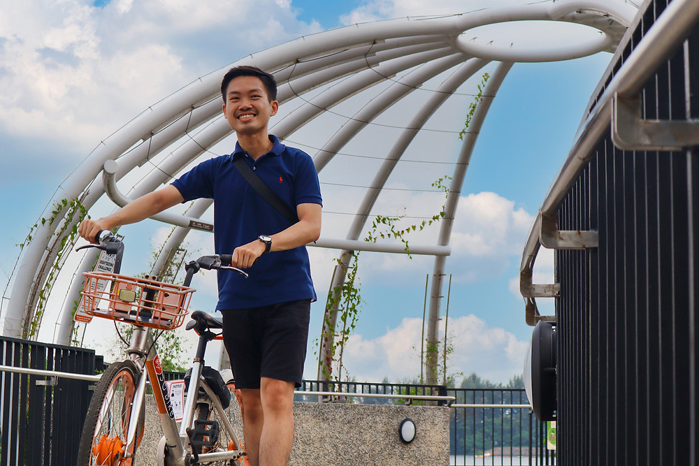 Guy pushing a bicycle on the Jewel Bridge at Sunset strip