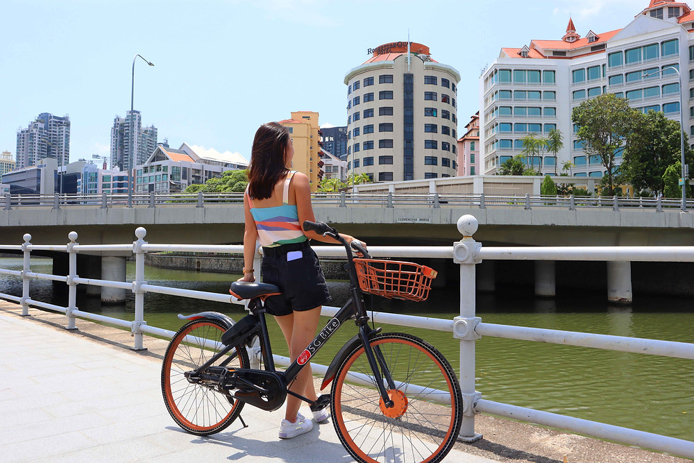 Girl leaning on SG Bike at Clemenceau Bridge