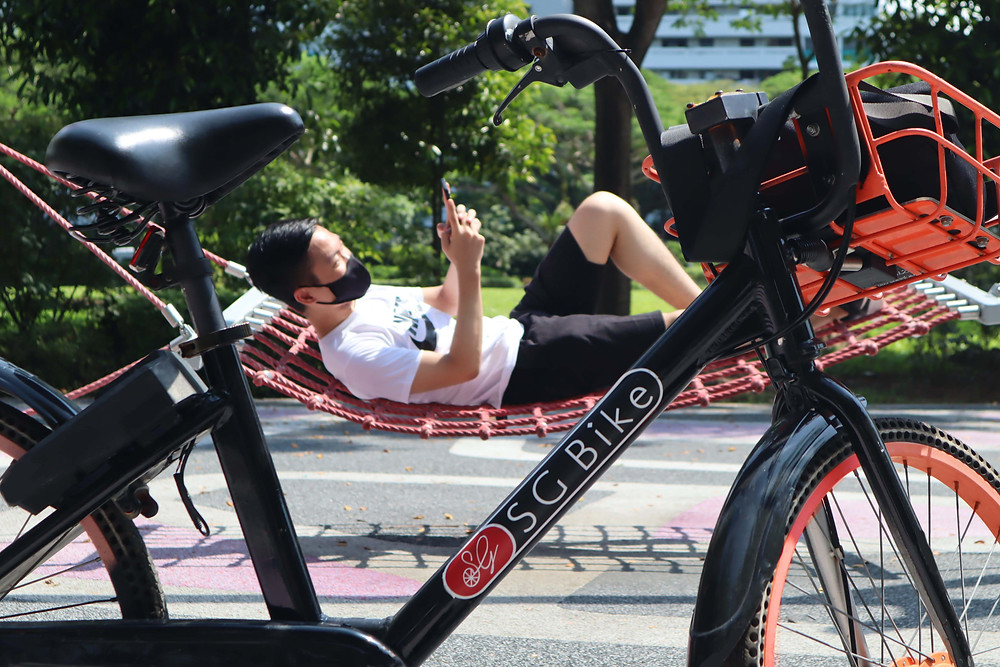 Guy lying on hammock with SG Bike in front