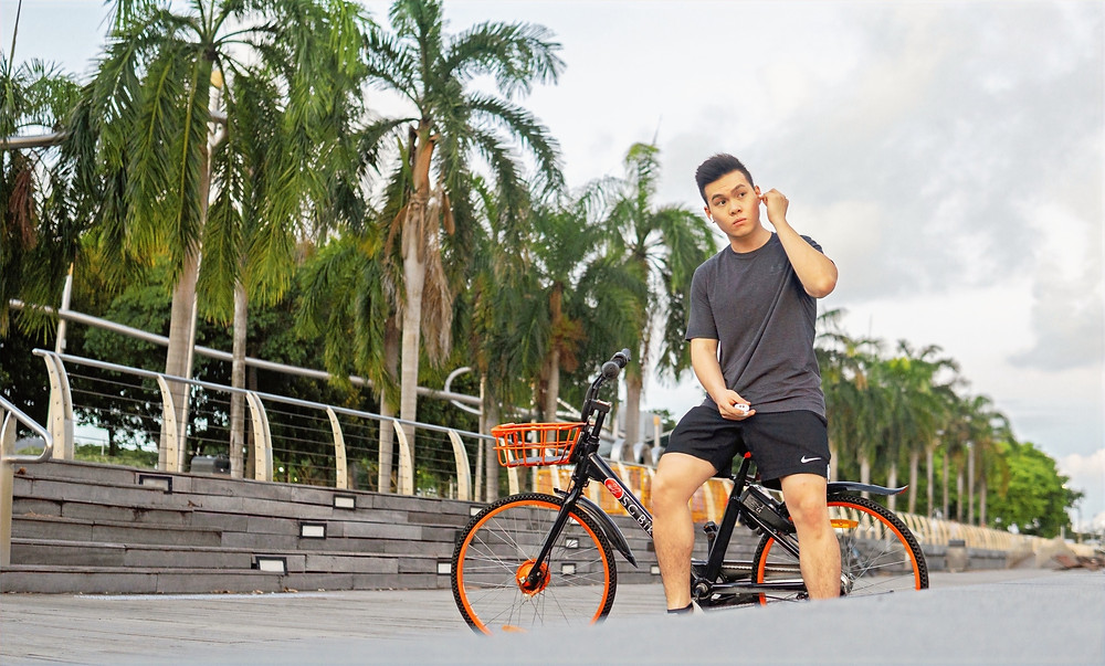 Man putting on earbuds while sitting on a bicycle along Marina Bay