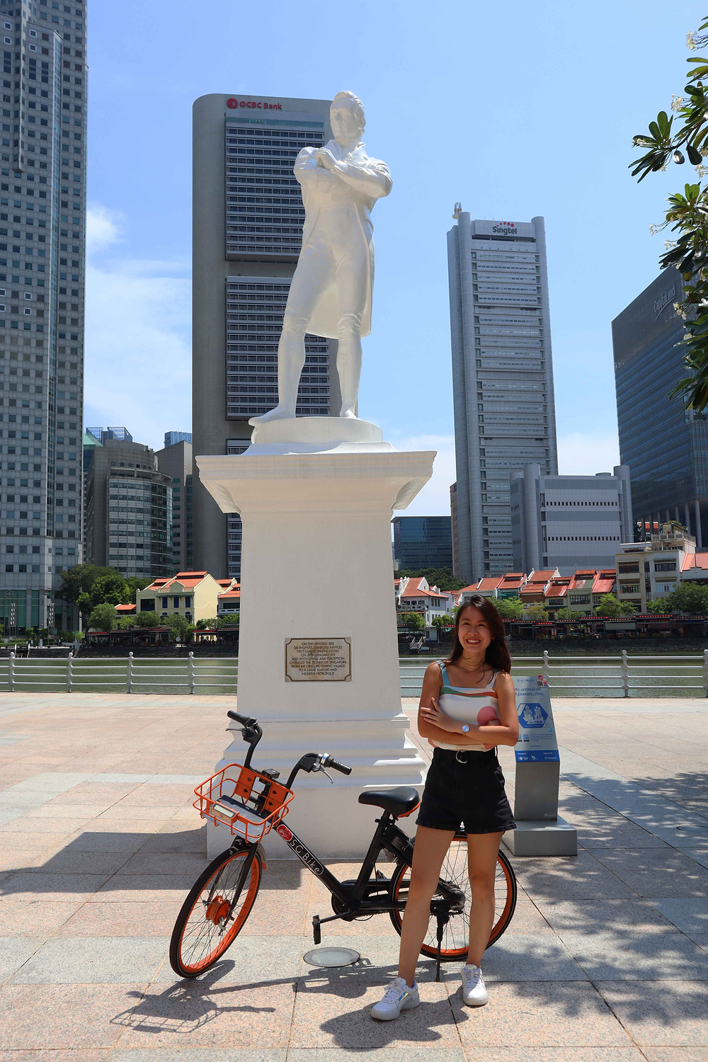 Girl posing under statue with SG Bike