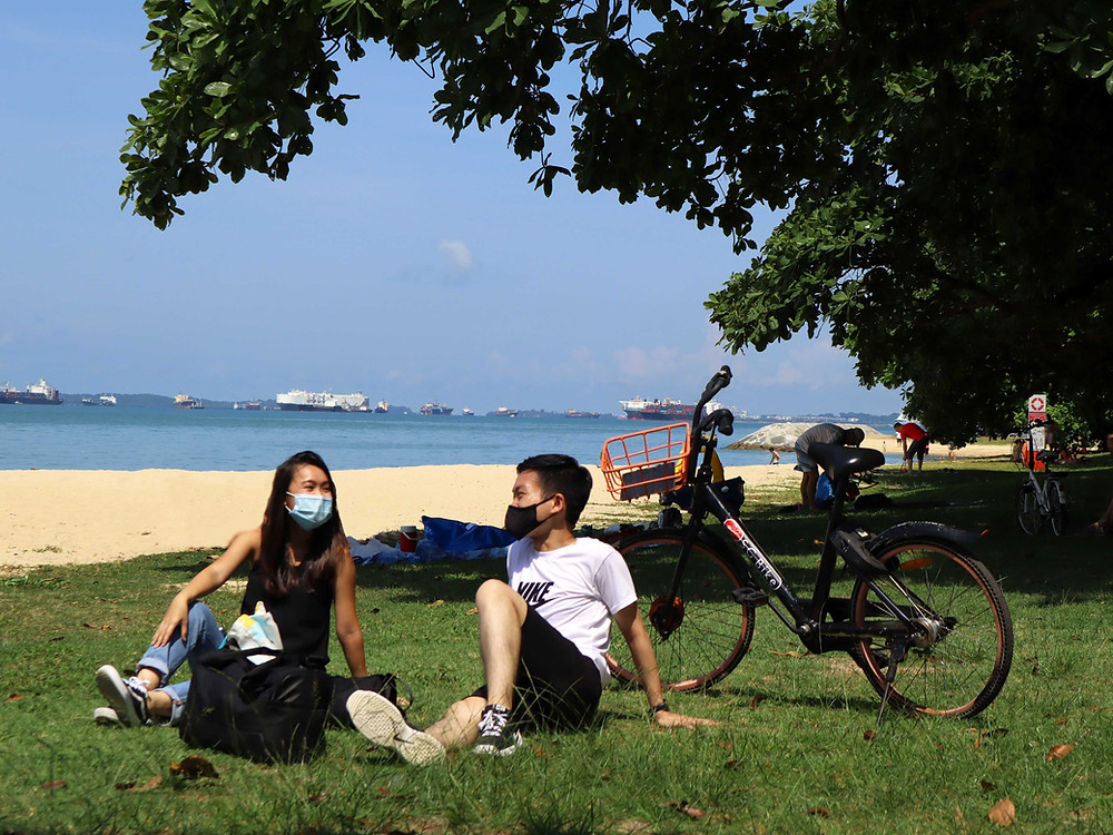Guy and girl sitting beside the beach in ECP with SG Bike