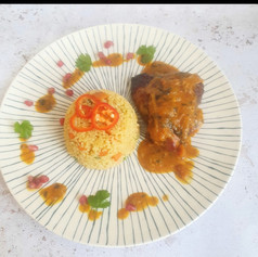 Roasted chicken with a butter chicken sauce served with rice.