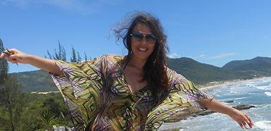 Élia Regina de braços abertos e ao fundo a praia.