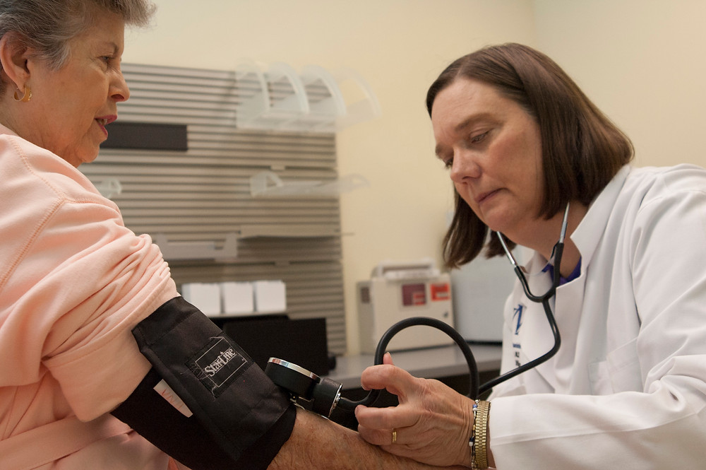 Dr. Mary Fox, Chief Medical Officer, takes woman's blood pressure.