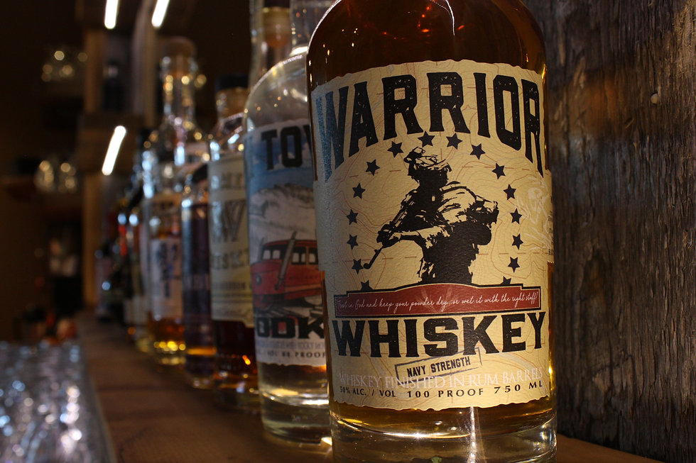 Close-up shot of Warrior Whiskey bottle with other bottles of spirits in the background