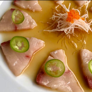 Yellowtail Sashimi with paper-thin jalapeño slices with light and tangy soy sauce dressing